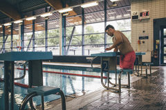 Ready to dive. Quadriplegic swimmer ready to dive in. He is getting on the platform with goggles on Royalty Free Stock Photo