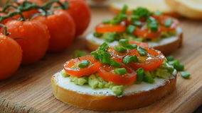 Ready to eat bruschetta with cream cheese, avocado tomatoes. Ready to eat bruschetta with cream cheese, avocado and chopped cherry tomatoes stock video footage