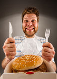 Ready to eat burger. Portrait of happy man with knife and fork ready to eat burger Royalty Free Stock Photos
