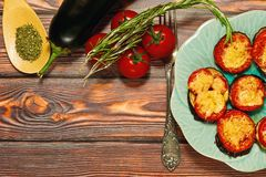 Grilled eggplants with cheese and tomatoes, mediterranean dish. Ready to eat dish of mediterranean cuisine - grilled eggplants with sweet tomatoes, yellow cheese Stock Image