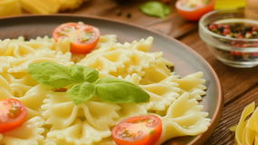 Ready to eat farfalle with cut tomatoes and basil stock video