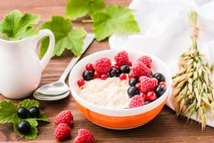 Ready-to-eat oatmeal with fresh raspberries and black currants. On a wooden table Royalty Free Stock Images