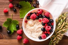 Ready-to-eat oatmeal with fresh raspberries and black currants. Top view Stock Photo