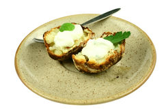 Ready to eat potato. Fresh baked potatoes with sauce on a plate isolated on white Royalty Free Stock Photography