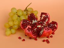 Ready to eat red ripe juicy pomegranate fruit with seeds and a bunch of sweet yellow grapes, healthy eating concept on an orange b. Ackground close up royalty free stock photo