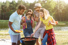 We are ready to eat this roast food. Happy young friends are making barbecue in the nature. They are standing near grill and smiling. Men and women are drinking Royalty Free Stock Image
