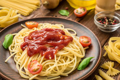 Ready to eat spaghetti with ketchup, tomatoes and basil Royalty Free Stock Image