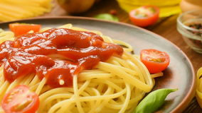 Ready to eat spaghetti with ketchup, tomatoes and basil stock footage