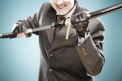 Ready to fight!. Young smiling businessman with sword in his arms ready to fight with rivals and to win. Business is a struggle concept, looking in the future Stock Photos