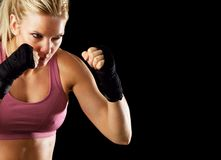 Ready to Fight. Portrait of a fitness woman ready to fight. Isolated on black with copy space stock photos