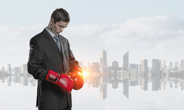 Always ready to fight. Businessman wear boxing gloves against modern cityscape Royalty Free Stock Photos