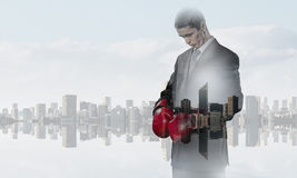 Always ready to fight. Businessman wear boxing gloves against modern cityscape Royalty Free Stock Image