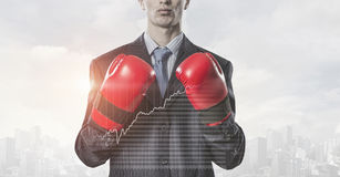Always ready to fight. Businessman wear boxing gloves against modern cityscape Stock Photography