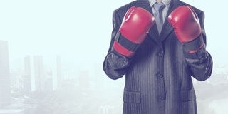 Always ready to fight. Businessman wear boxing gloves against modern cityscape Royalty Free Stock Photo