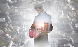 Always ready to fight. Businessman wear boxing gloves against modern cityscape Royalty Free Stock Photography
