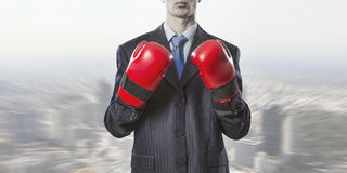Always ready to fight. Businessman wear boxing gloves against modern cityscape Stock Photos