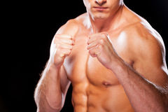 Ready to fight. Close-up of serious young shirtless man looking at camera while standing against black background Stock Photo
