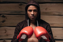 Ready to fight. Confident young African man in hooded shirt and boxing gloves looking at camera while standing against wooden background Stock Photos