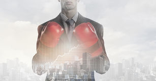 Always ready to fight . Mixed media. Businessman wear boxing gloves against modern cityscape Stock Image