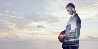 Always ready to fight . Mixed media. Businessman wear boxing gloves against modern cityscape Royalty Free Stock Photos