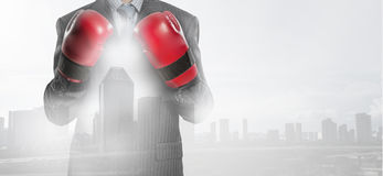 Always ready to fight . Mixed media. Businessman wear boxing gloves against modern cityscape Royalty Free Stock Photo