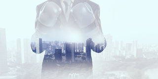 Always ready to fight . Mixed media. Businessman wear boxing gloves against modern cityscape Stock Photos