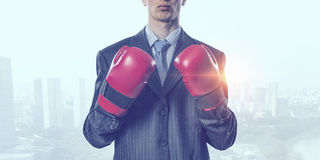 Always ready to fight . Mixed media. Businessman wear boxing gloves against modern cityscape Stock Images