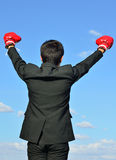 Ready to fight over blue sky. Businessman and hand boxing glove ready to fight over blue sky Royalty Free Stock Photography