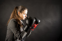 Ready to fight. Portrait of beautiful and young business woman wearing boxing gloves Stock Photos