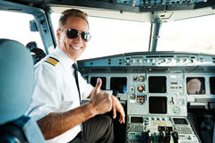 Ready to flight. Rear view of confident male pilot showing his thumb up and smiling while sitting in cockpit Royalty Free Stock Images