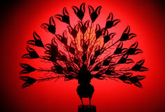 Ready to fly. Handmade peacock sculplture in red backlit royalty free stock image