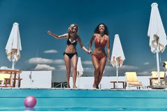 Ready to get refreshed?. Full length of two attractive young women in bikini preparing to jump into the pool Royalty Free Stock Image