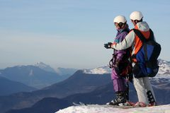 Ready to go. Instructor show the paraglider the way to ski off the mountain Stock Images