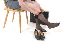 Ready to go. Woman in business attire putting on her pantyhose Stock Image
