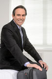 Ready to go. Cheerful mature businessman sitting on the sofa at Royalty Free Stock Photo