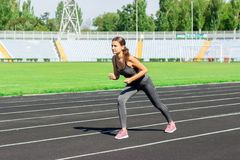 Ready to go. Close up photo of female athlete on high start starting line. Girl on Stadium track, preparing for a run. Sports and. Healthy concept royalty free stock images