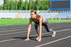 Ready to go. Close up photo of female athlete on low start starting line. Girl on Stadium track, preparing for a run. Sports and. Healthy concept royalty free stock images