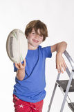 Ready to go. Young boy leaning a ladder and holding a rugby league ball in the air while smiling at the camera Stock Photos