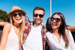Always ready to have some fun. Three young happy people looking at camera and smiling while enjoying road trip in convertible stock photo