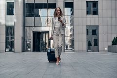 Always ready to help. Full length of young woman in suit pulling luggage and smiling while walking outdoors royalty free stock photo