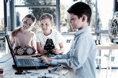 Supportive children working on technical project together. Always ready to help. Selective focus on a girl and boy looking t their friend at a laptop and helping stock photos