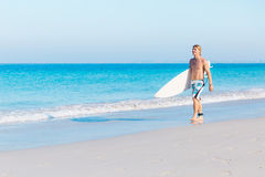 Ready to hit waves. A young surfer with his board on the beach Stock Image