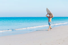 Ready to hit waves. A young surfer with his board on the beach Royalty Free Stock Images