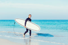 Ready to hit waves. A young surfer with his board on the beach Stock Photos
