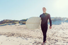 Ready to hit waves. A young surfer with his board on the beach Stock Images