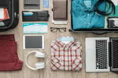 Ready to leave. Getting ready for a trip and packing a suitcase before leaving; accessories, clothing and personal items on a desktop, travel and vacations Stock Photos