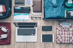 Ready to leave. Travel equipment on a desktop: clothing, wallet, laptop, tablet, smartphone and personal accessories, travel and vacations concept Stock Photos