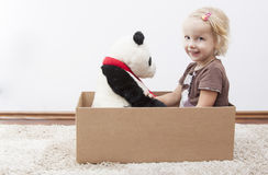 Ready to move. Blond little girl with her teddy bear ready to move Royalty Free Stock Photo