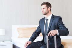 Ready to new business trip. Confident young businessman in formalwear carrying suitcase and smiling while sitting on the bed in hotel room Stock Photo