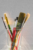 Ready to paint. A close-up still life of various sized artist's brushes in front of a blank stretched canvas Stock Photos